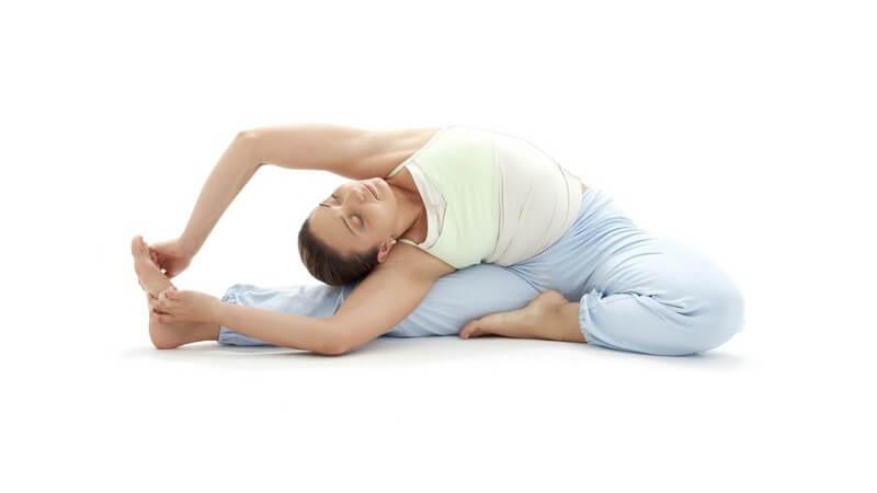 Dunkelhaarige Frau bei Yoga Übung im Sitzen, hält sich an rechtem Fuß fest