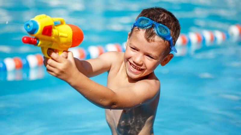 Junge im Schwimmbecken trägt eine Schwimmbrille auf der Stirn und spritzt mit einer Wasserpistole