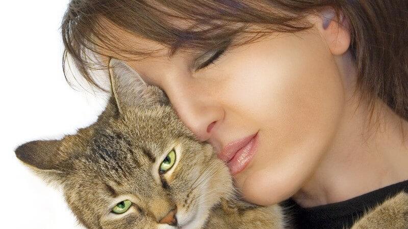 Junge Frau schmiegt ihr Gesicht an das ihrer Katze