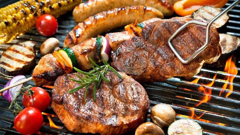 Grillrost voll mit Steaks, Spießen, Würstchen und Gemüse