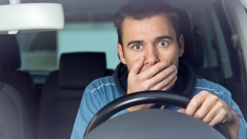 Junger Autofahrer hinter dem Lenkrad, hält sich unter Schock die Hand vor den Mund