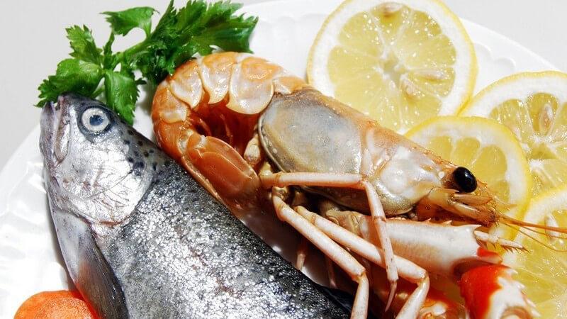 Nahaufnahme weißer Teller mit Meeresfrüchten: Garnele und Fisch an Zitronenscheiben und Petersilie
