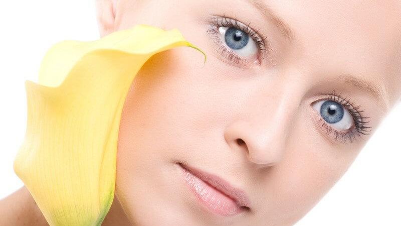 Gesicht einer jungen Frau mit blauen Augen, sie hält gelbe Blume und schaut in Kamera