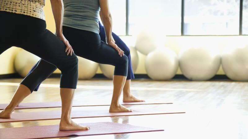 3 Frauenbeine in blauen Leggins, jeweils zur Seite auf Yogamatten