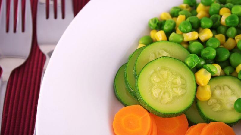 Frisches Gemüse in weißem Teller, daneben zwei Gabeln