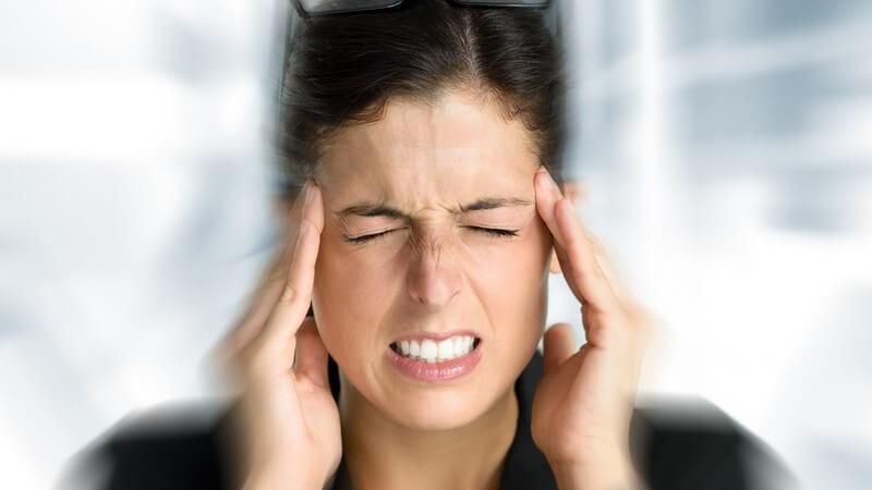 Frau vor verschwommenem Hintergrund fasst sich mit geschlossenen Augen und Kopfschmerzen an die Schläfen