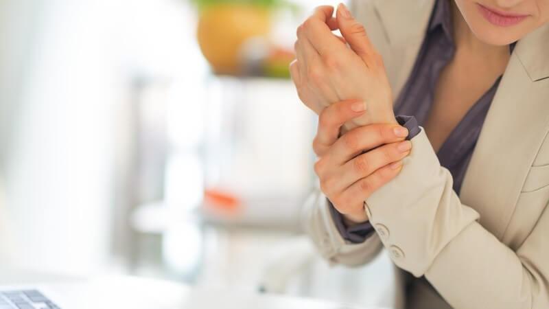 Businessfrau sitzt am Schreibtisch und fasst sich vor Schmerzen ans Handgelenk