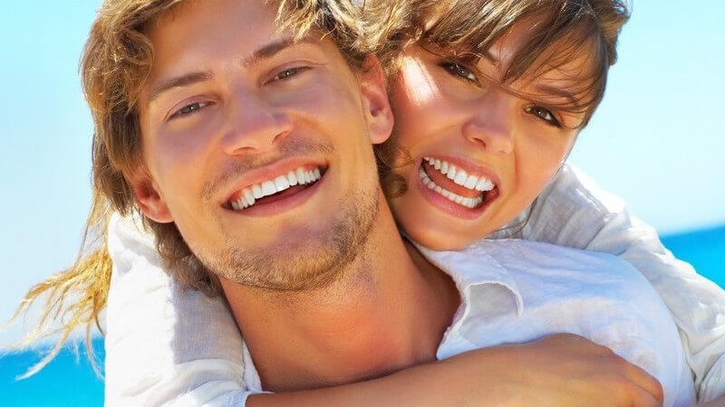 Junges Paar am Strand, er trägt sie auf dem Rücken, beide lachen