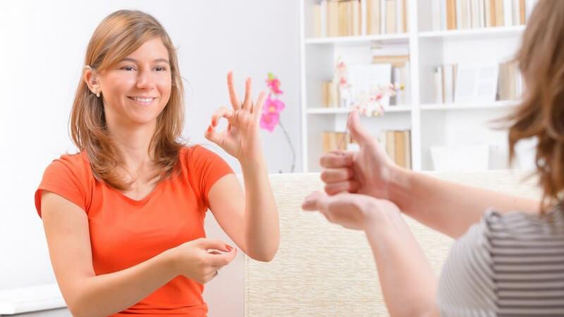 Taube Frau beim Nachahmen und Erlernen der Gebärdensprache
