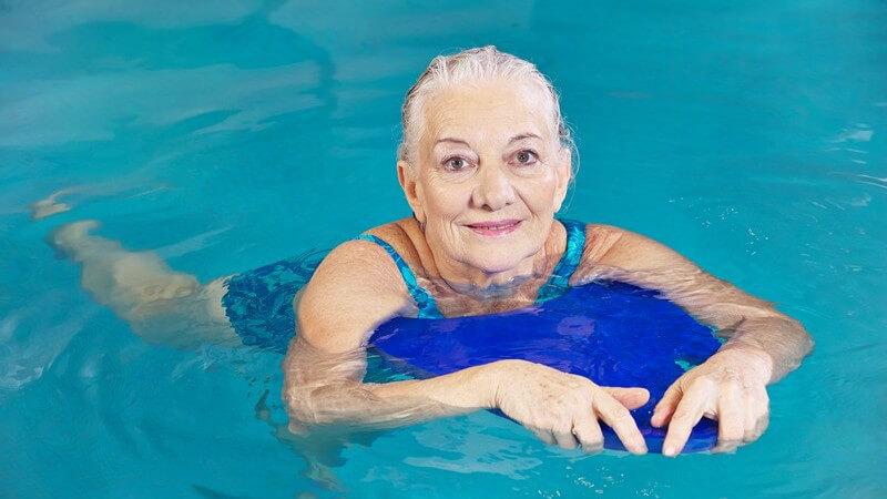 Seniorin beim Schwimmen mit einem blauen Schwimmbrett
