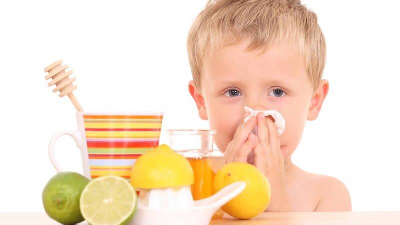 Kleiner Junge mit Erkältung putzt sich Nase, davor Tee, Limetten, Zitronen, Honig auf Tisch