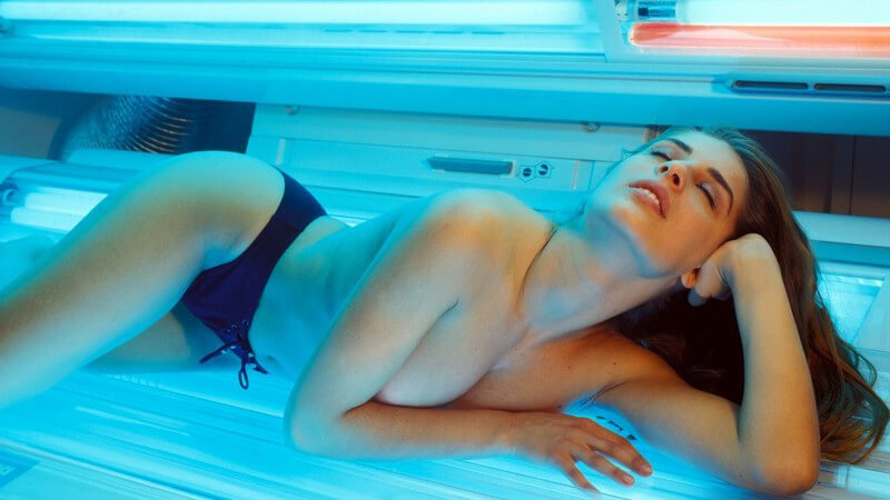 Junge Frau entspannt im Solarium
