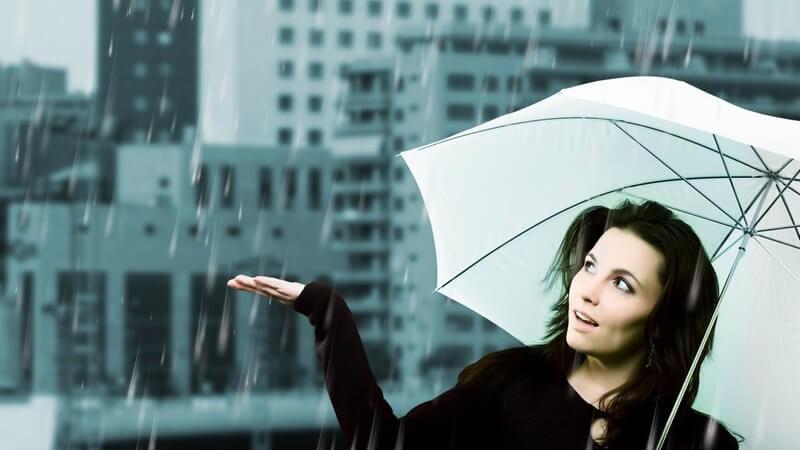 Dunkelhaarige Frau geht unter weißem Regenschirm an Regentag durch die Stadt