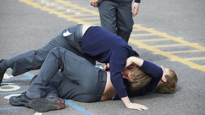 Zwei Jungen in Schuluniform raufen auf dem Schulhof