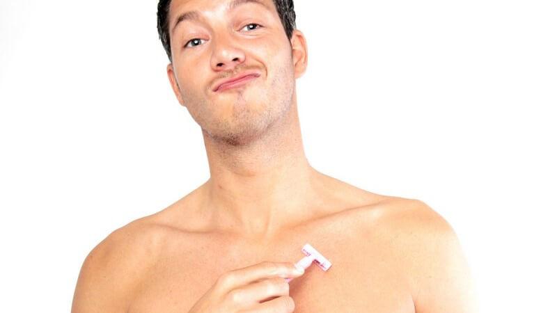 Junger, dunkelhaariger Mann mit nacktem Oberkörper beim Rasieren der Brust