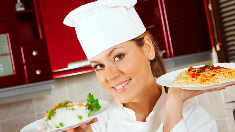 Junge Köchin mit einem Reis- und einem Spaghettiteller in den Händen