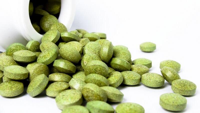 Grüne Pillen, die aus einer weißen Flasche kullern