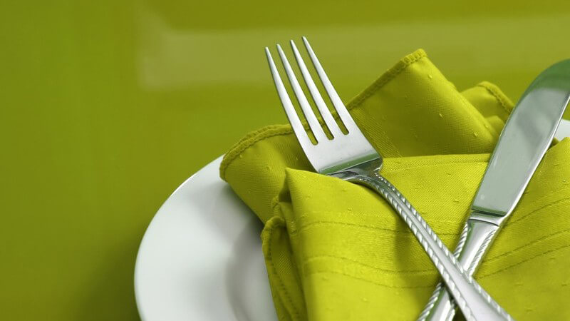 Besteck auf grüner Serviette auf weißem Teller, grüner Hintergrund