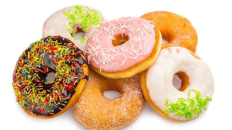Unterschiedliche Donuts mit Streuseln und Zuckerguss vor weißem Hintergrund