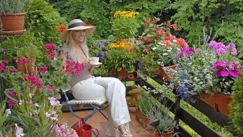 Junge Frau mit Strohhut sitzt auf Balkon umgeben von bunten Blumen, Kaffeetasse in Hand