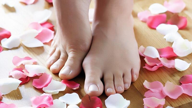 Nackte Frauenfüße auf Holzboden umgeben von Rosenblättern