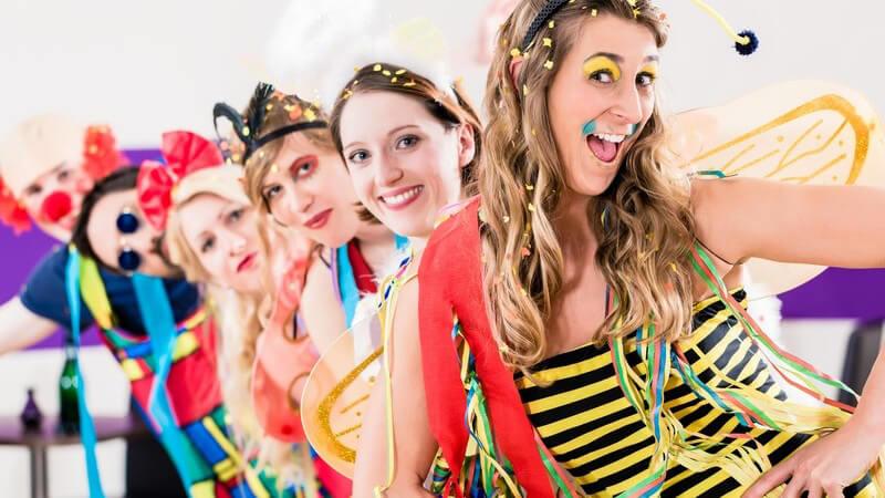 Junge Leute in Karnevalskostümen wie Biene und Clown stehen in einer Reihe