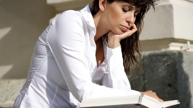 Junge Frau in weißer Bluse sitzt auf Treppenstufen und liest mit aufgestütztem Kopf in Buch