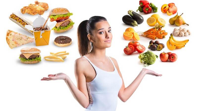 Ungesunde (Fast Food) und gesunde Nahrungsmittel (Obst und Gemüse) schweben über den Händen einer sportlichen Frau