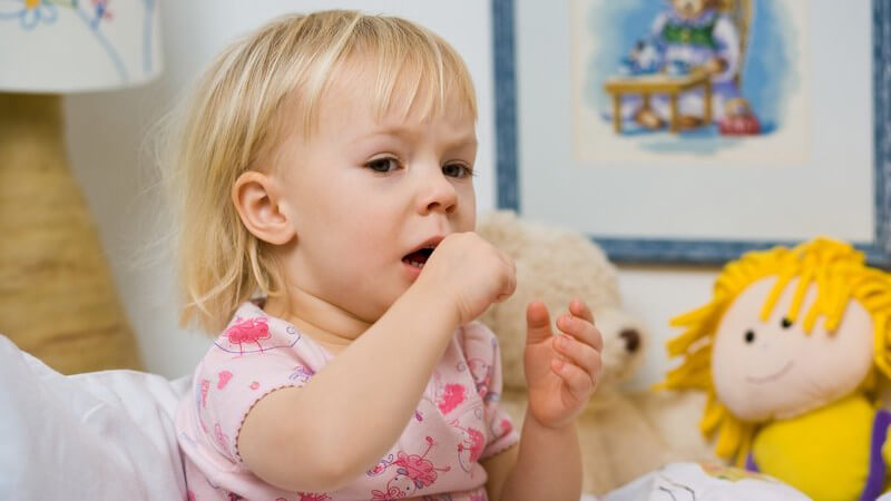 Kleines krankes Mädchen sitzt im Bett und hustet
