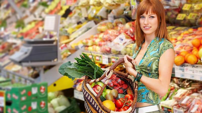 Rothaarige Frau in grünem Outfit mit Obst-und-Gemüse-Korb in der Hand in einem Supermarkt