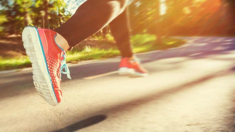 Joggerin in roten Laufschuhen und schwarzer Laufhose läuft im Sonnenschein eine Straße entlang