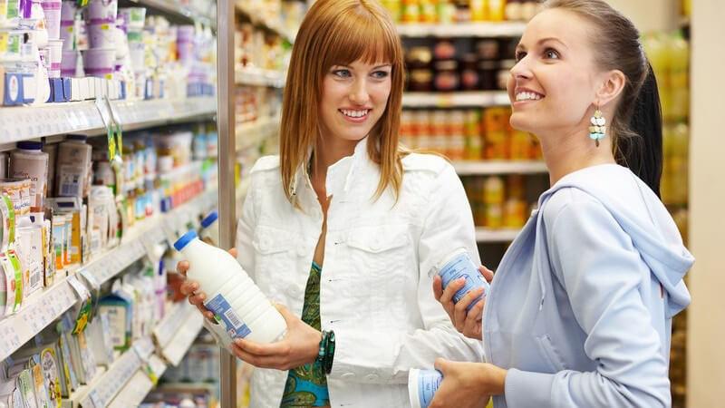 Zwei lächelnde Frauen vor Regal im Supermarkt