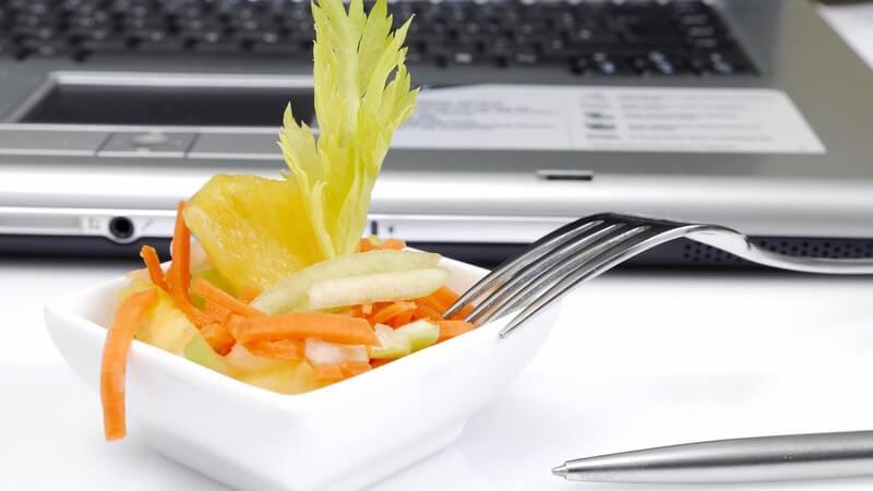 Kleine Schale mit Salat auf Schreibtisch vor Notebook