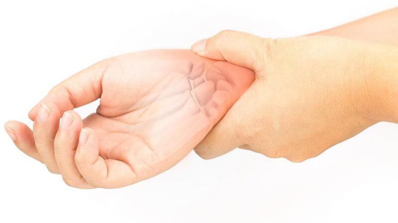 Hand auf schmerzendem Handgelenk, die Handgelenkknochen scheinen durch (Fotomontage)