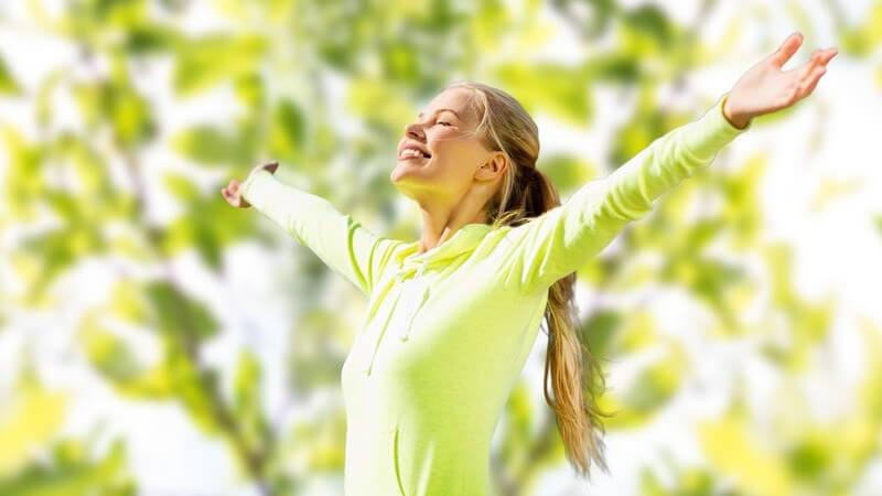 Sportlerin in grüner Sportkleidung steht im Grünen und reißt glücklich die Arme hoch
