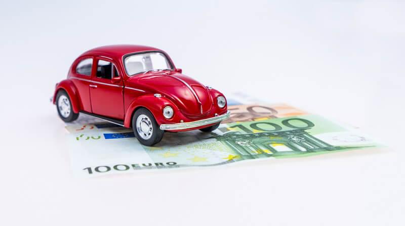 Automodell eines roten Käfers steht auf Euro-Geldscheinen