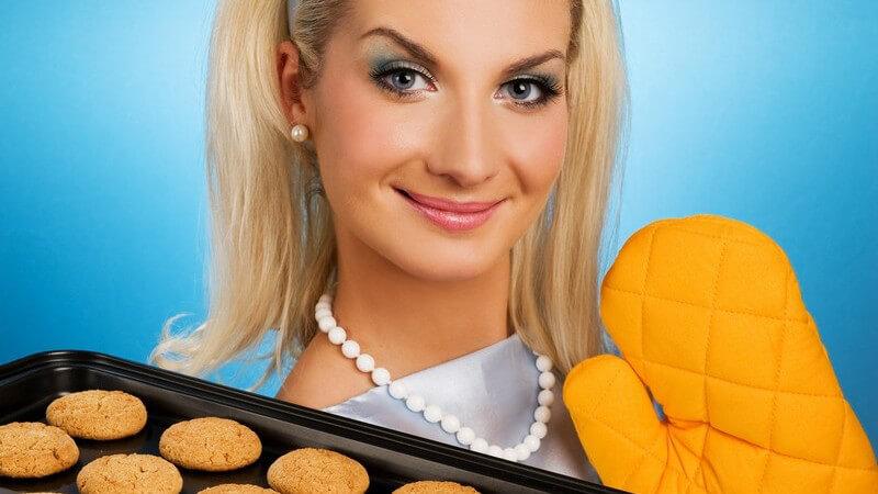 Junge Frau im Kleid mit gelben Backhandschuhen hält Backblech mit Keksen in die Kamera