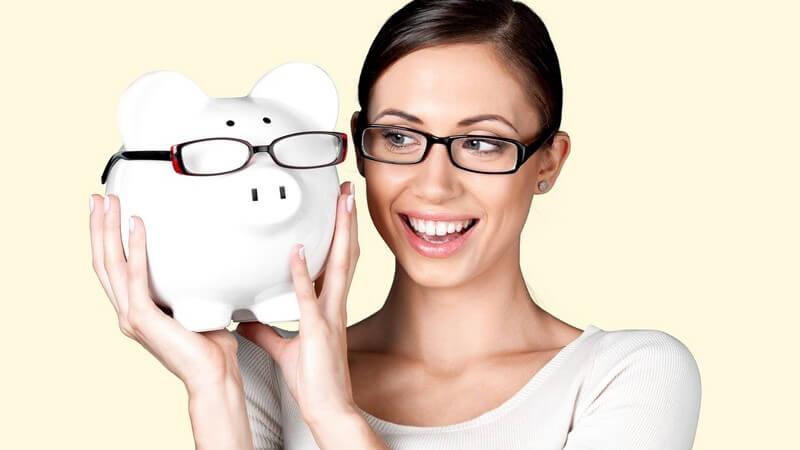 Frau mit Brille hält ein weißes Sparschwein mit Brille hoch