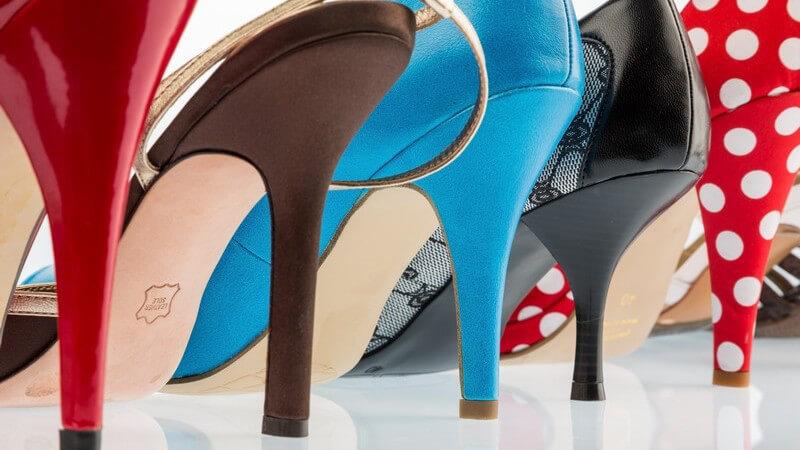 Fünf High Heels in unterschiedlichen Farben auf spiegelndem Untergrund