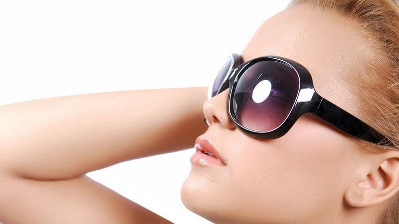 Seitenansicht junge Frau trägt Sonnenbrille mit großen Gläsern und schaut nach oben