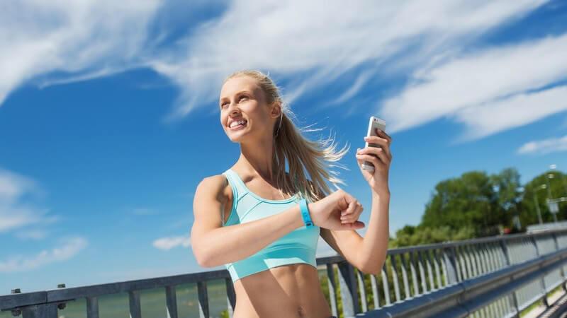 Blonde Joggerin steht auf einer Brücke und checkt ihren Puls mit Fitnessarmband und Smartphone