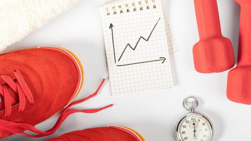 Turnschuhe, Stoppuhr, Hanteln und eine Zeichnung über Trainingsfortschritte
