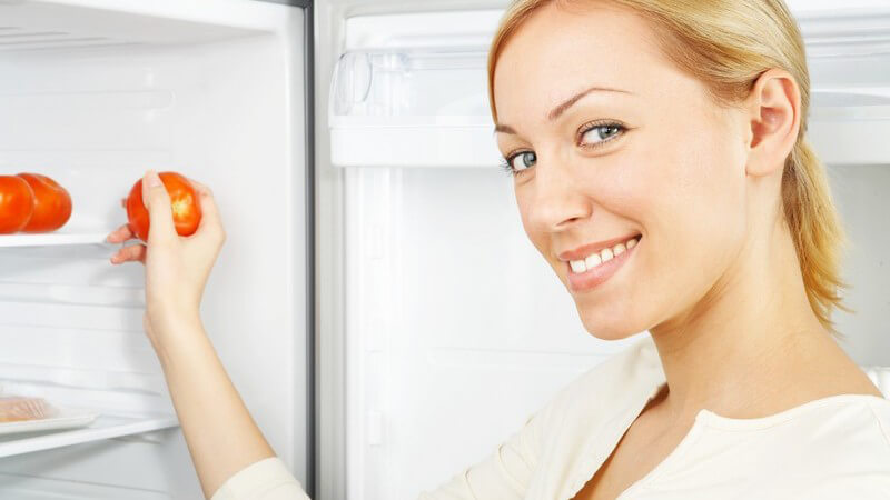 Blonde Frau am Kühlschrank holt Tomaten raus