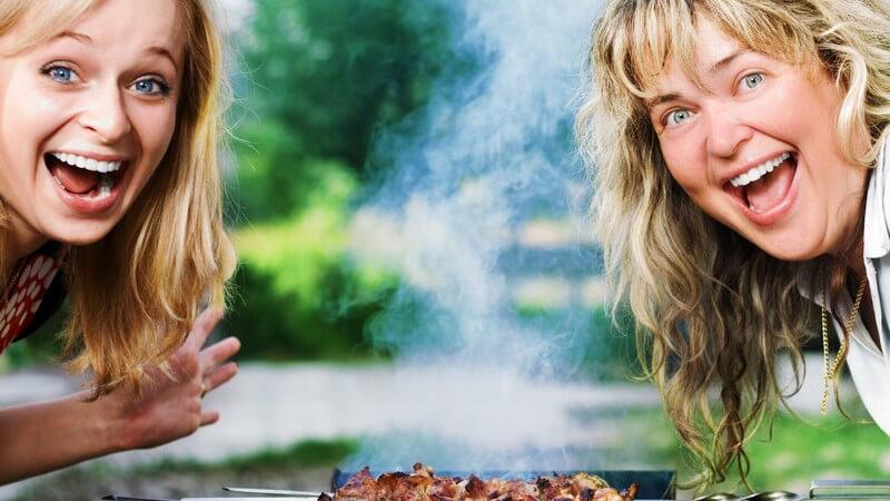Zwei lachende Frauen über Grill mit Fleischspießen