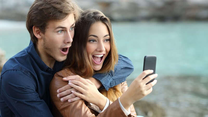 Junges Paar sitzt zusammen draußen und guckt schockiert auf ein Smartphone