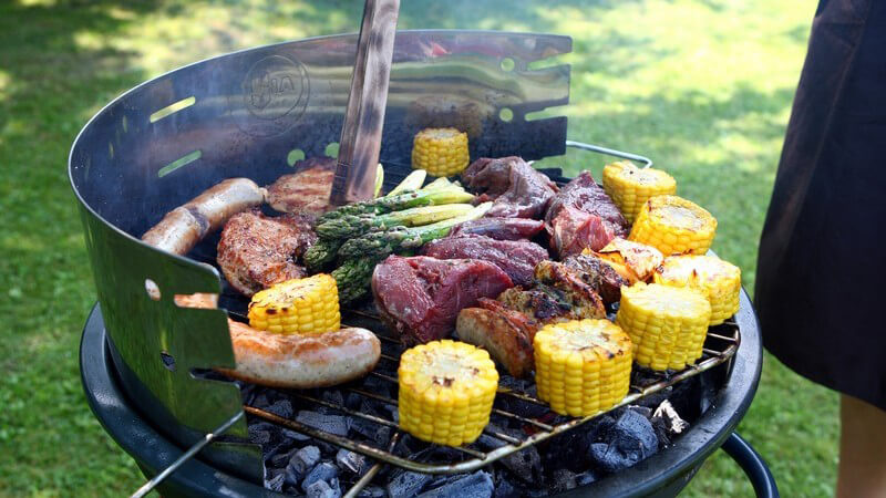 Grill auf Wiese mit Fleisch, Spargel, Maiskolben