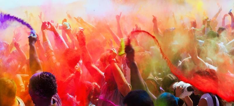 Holi Festival: Menschenmenge wirft mit bunten Farben um sich und tanzt