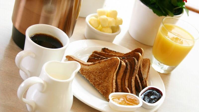 Frühstückstisch mit Toasts, Kaffee, Sahne, Orangensaftglas, Marmelade auf Holztisch