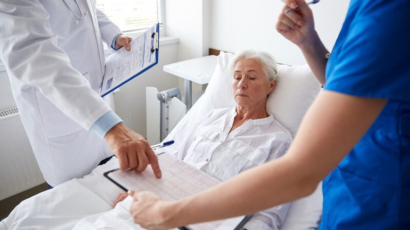 Arztvisite bei einer älteren Patientin im Krankenhausbett, Arzt und Krankenschwester halten ein Klemmbrett in der Hand