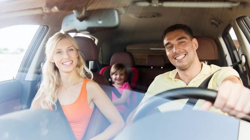 Junge Familie fährt lächelnd mit dem Auto, kleines Mädchen im Kindersitz